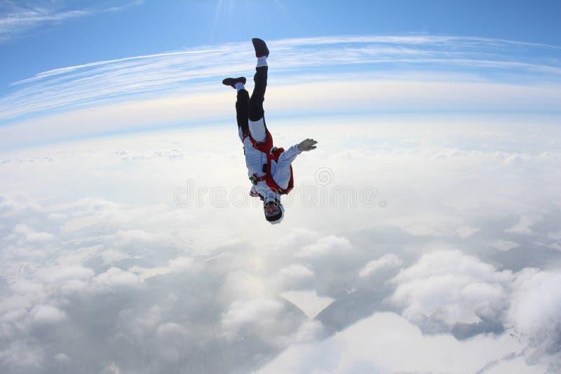 skydiving Skydiver in hoofd onderaan positie valt boven wolken stock afbeelding