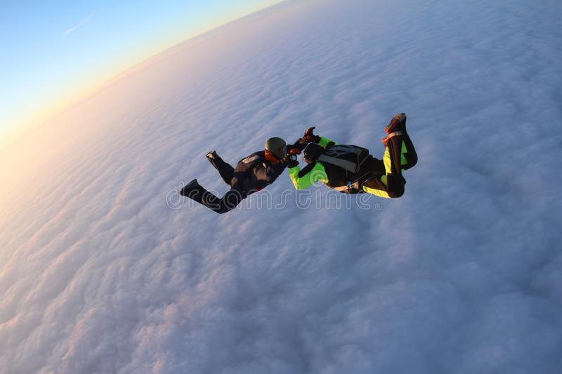 Skydiving. Sunset jump. Two skydivers are above pink clouds. Sunset jump. Two skydivers are falling above pink clouds. They hold each other royalty free stock images