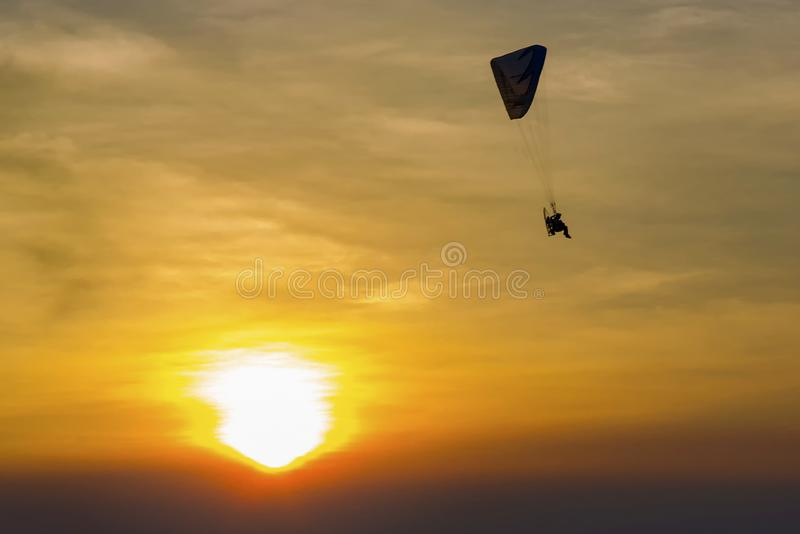 Skydiving sunset landscape of parachutist flying in soft focus. Para-motor flying silhouette with sun set. royalty free stock images