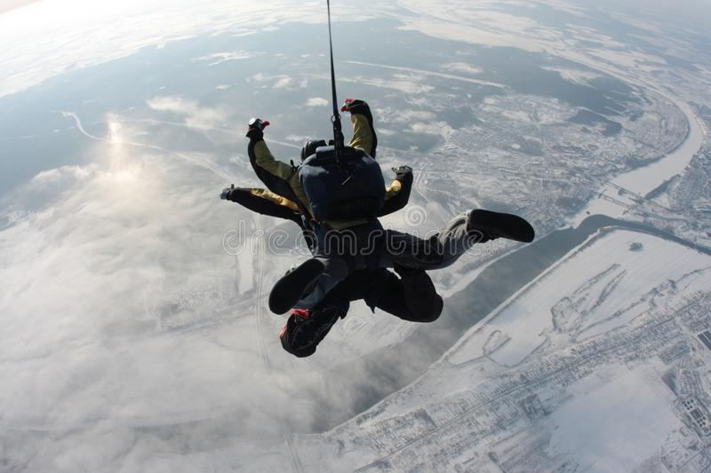 Skydiving tandem jumping from the plane against the background of the earth stock images