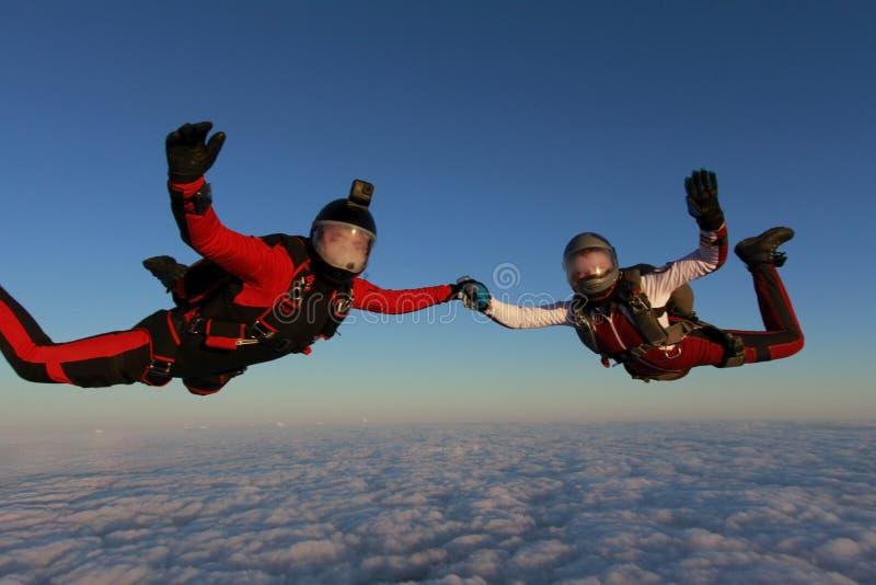 skydiving Två skydivers flyger i solnedgånghimlen arkivfoton