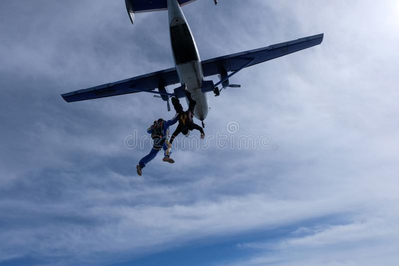 Skydiving. Two skydivers are flyingin the sky. Skydiving. Two skydivers are flying in the sky. White clouds and blue sky are in the background stock photography
