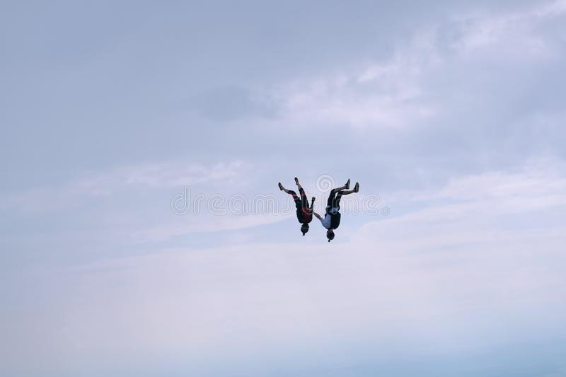 Skydiving. Two sportsmen are flying in the sky. Freefly skydiving.  Two skydivers are flying in the cloudy sky in head down position stock photos