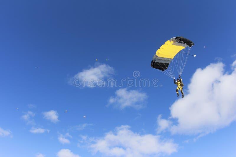 skydiving Un skydiver del yellowsuit está en el cielo azul imagen de archivo