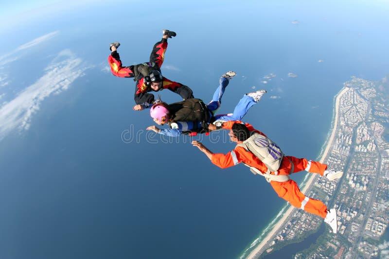 Skydivingsgroep over de kust stock afbeelding