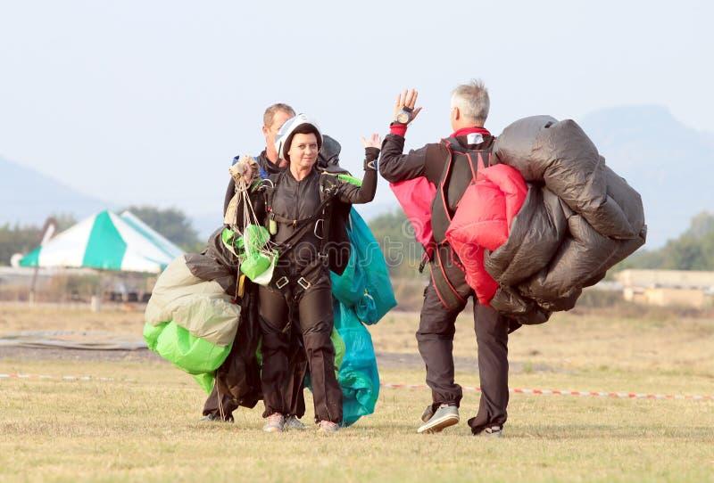 Skydivingsteam die elkaar hoogte vijf na succesvol art. geven royalty-vrije stock afbeelding