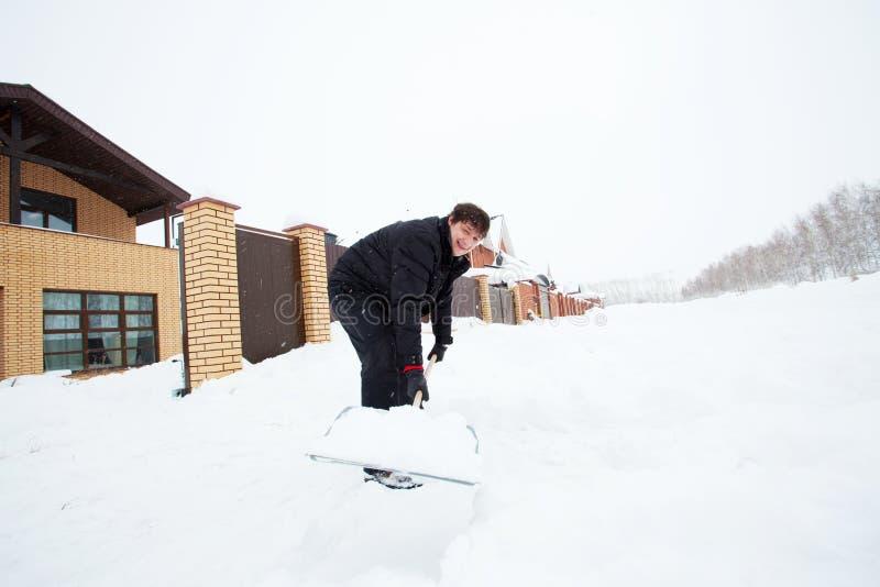 Skyffel för manrengöringsnö på vintern fotografering för bildbyråer