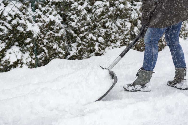 Skyffla snö på trottoar royaltyfri fotografi
