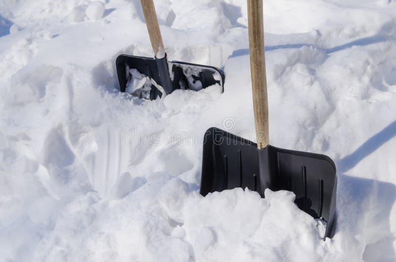 Skyfflar som klibbas i snödriva royaltyfria bilder