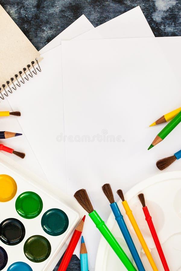 Skyla över brister vattenfärgen målar, borstar för att måla, färgblyertspennor arkivbilder