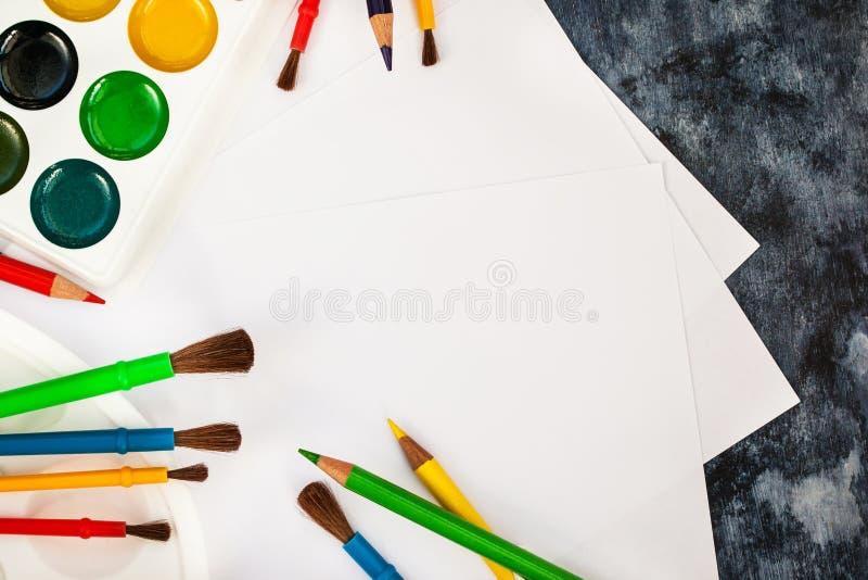 Skyla över brister vattenfärgen målar, borstar för att måla, färgblyertspennor arkivbild