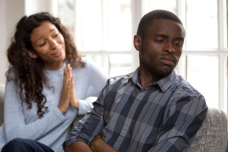 Skyldig afrikansk kvinna som ber om ursäkt fråga svart make för forgiv royaltyfri bild