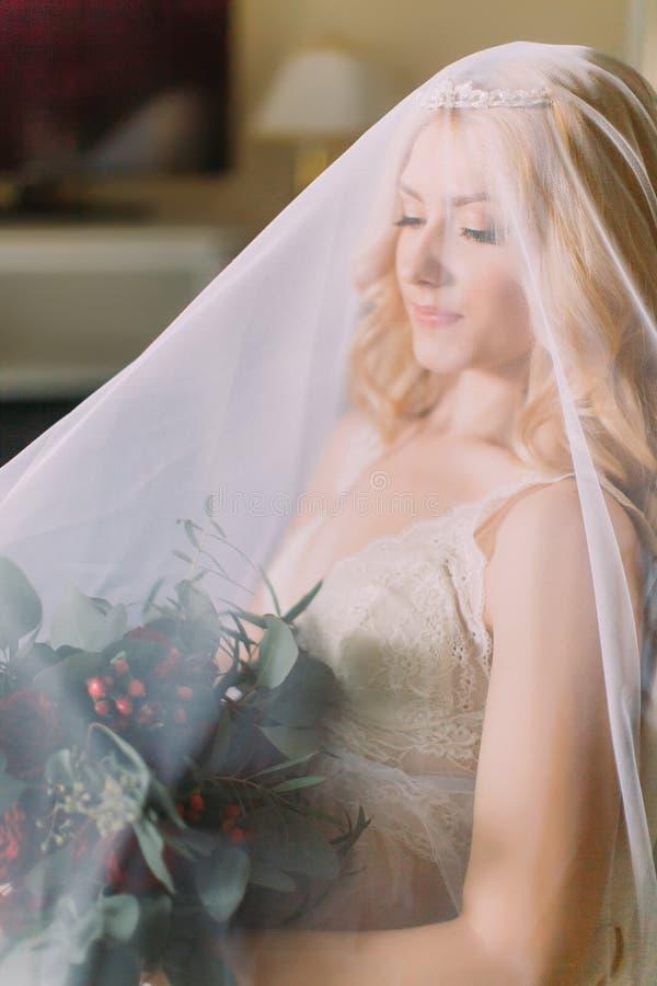 Skyler den iklädda hållande buketten för den sexiga blonda bruden och den vita underkläderna endast royaltyfria foton