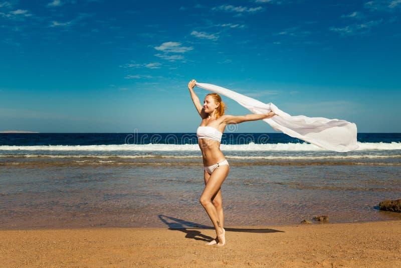 Skyler hållande vit för kvinnan på stranden royaltyfri fotografi