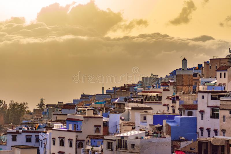Blue and White Colored Homes and Buildings in Chefchaouen Morocco during a Golden Sunset. A skyline of blue and white color homes and buildings with large clouds stock photography