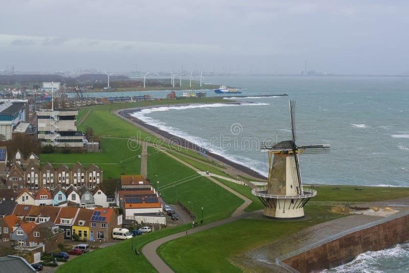Skyline bonita do moinho de vento do vlissingen com algumas casas e da vista no mar, paisagem holandesa típica, cidade popular em foto de stock