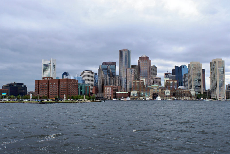 Skyline from boston harbor. View of the boston skyline from boston harbor showing various skyscrapers from different eras. The sea is choppy and the sky cloudy stock photography