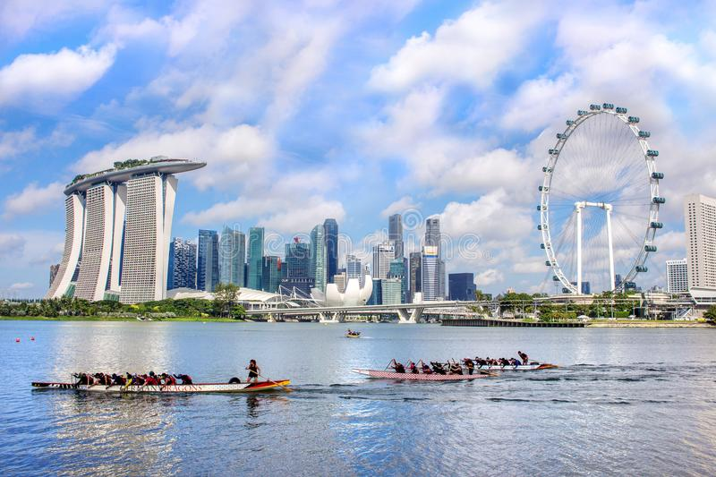Skyline of the city financial district with Marina Bay Sands hotel and Singapore Flyer and dragon boat practicing stock photos