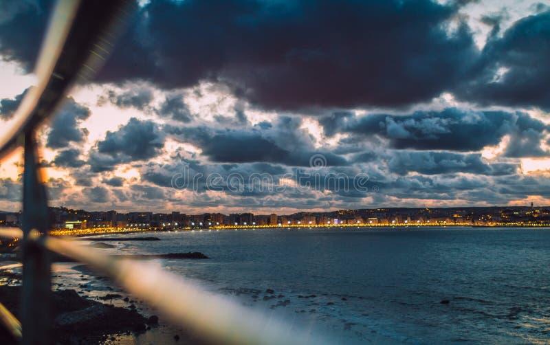 Skyline da cidade na noite sob a formação bonita da nuvem T?nger, Marrocos fotografia de stock royalty free