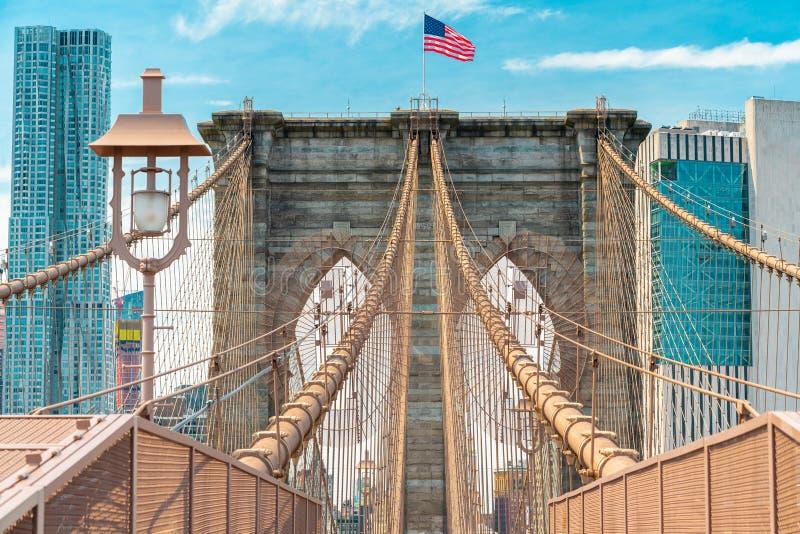 Skyline da ponte e do Manhattan de Brooklyn Detalhes arquitetónicos, cabos de aço icônicos, bandeira americana New York City imagens de stock royalty free