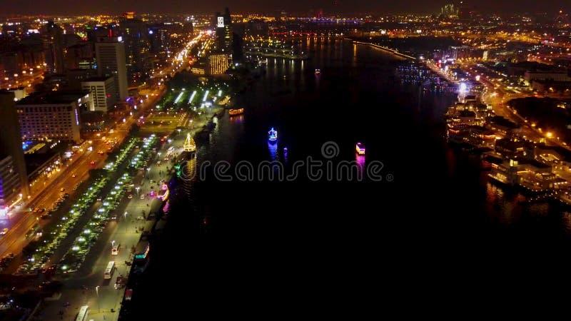 Skyline de Dubai na noite com a cidade bonita com luzes perto dela a estrada a mais ocupada do ` s Opinião do porto de Dubai da n imagem de stock royalty free