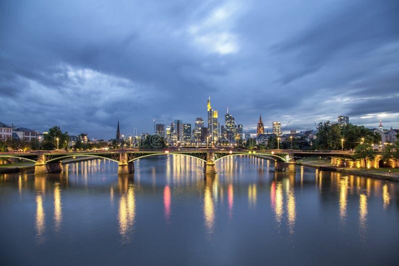 A skyline de Francoforte na ponte e nas luzes da noite nubla-se imagem de stock