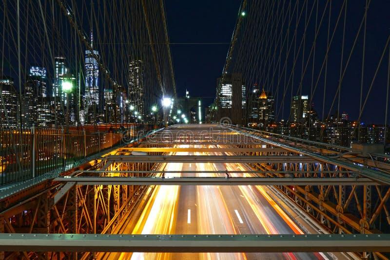 Skyline de New York City, tráfego na ponte de Brooklyn na noite, nas construções de Manhattan e nos arranha-céus foto de stock