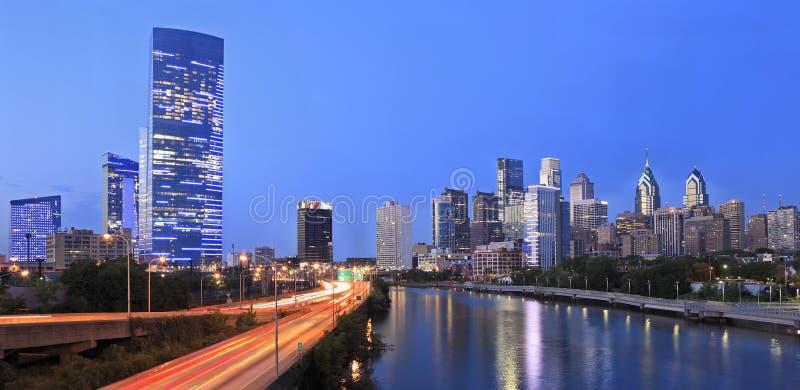 Skyline de Philadelphfia iluminada no crepúsculo e no rio de Schuylkill foto de stock