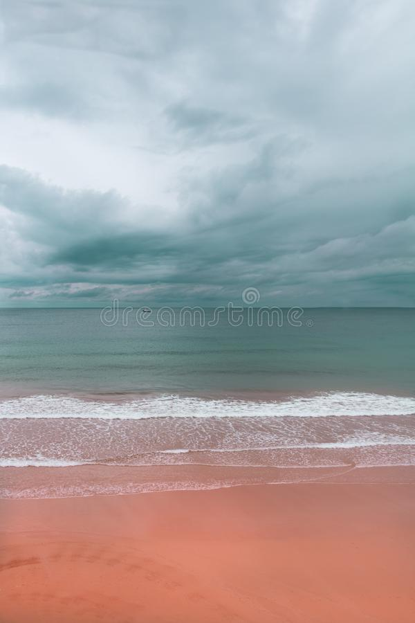 Skyline de uma praia com areia cor-de-rosa e o céu nebuloso imagem de stock royalty free