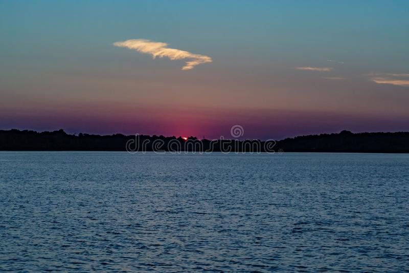 Clear outline of the disappearing sun at Sunset with beautiful skyline over lake Zorinsky Omaha Nebraska. Skyline of the disappearing setting sun with beautiful stock image