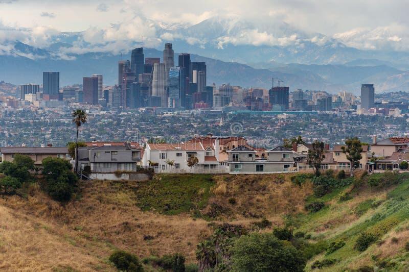 Skyline do centro de Los Angeles com casas e as montanhas snowcapped fotografia de stock
