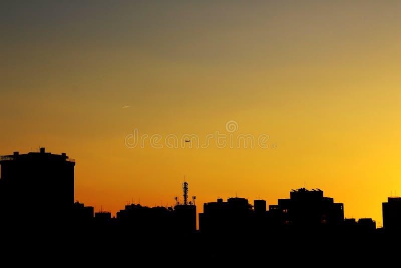 Skyline at golden hour in Sao Paulo. Vista da hora de ouro em São Paulo com o detalhe de um avião sobrevoando a cidade stock photo