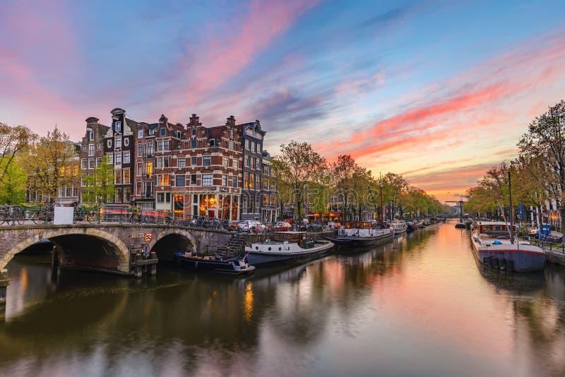 Skyline holandesa da cidade do por do sol de Amsterdão no canal foto de stock royalty free