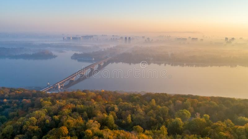 Skyline, Kiev city with beautiful morning sky. Pedestrian bridge. Left bank the Dnieper River. Aerial view. Sunrise over city stock images