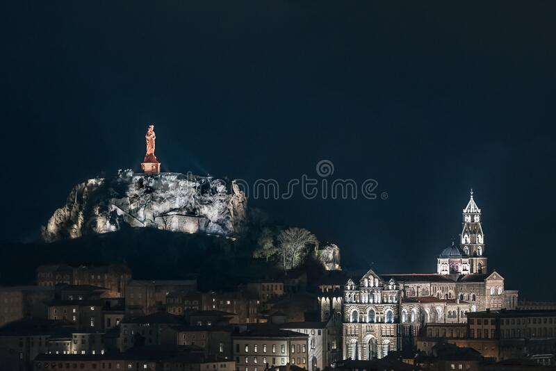 Skyline Le Puy-en-Velay in central France at twilight time; Cathedral and red christian statue.  royalty free stock images