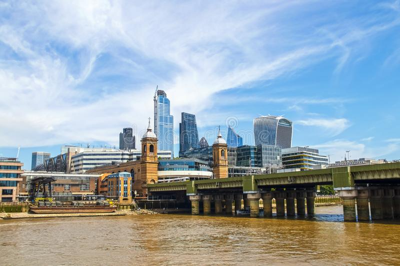 Skyline of London viewed over Thames River and London Bridge under beautiful blue sky with whispy clouds.  royalty free stock photo