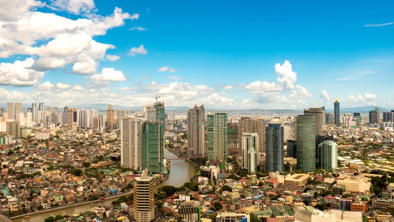 Skyline of Manila by the River Pasig. View on high rise condo buildings in Makati by the River Pasig as clouds pass through the blue sky in Manila, Philippines royalty free stock photography