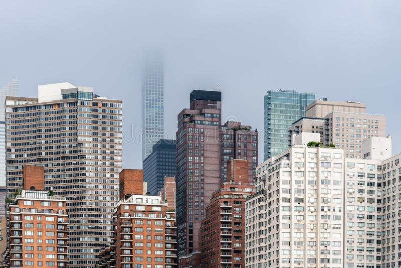 Skyline of Midtown of New York City. Skyline of Midtown of NYC from East River in Roosvelt Island a misty day stock photo
