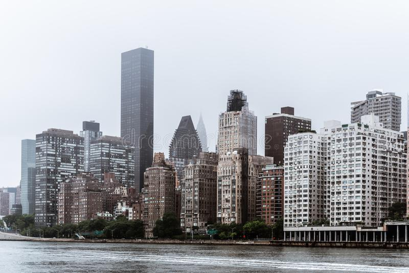 Skyline of Midtown of New York City. Skyline of Midtown of NYC from East River in Roosvelt Island a misty day stock image