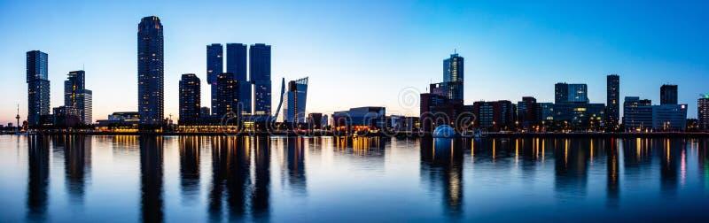 Skyline-Nachtpanorama Rotterdams die Niederlande Stadttürme belichteten, Reflexionen auf dem Wasser, Sonnenuntergangzeit lizenzfreies stockbild