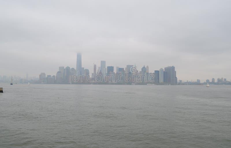 Skyline obscura do Lower Manhattan em um dia de mola nublado imagens de stock