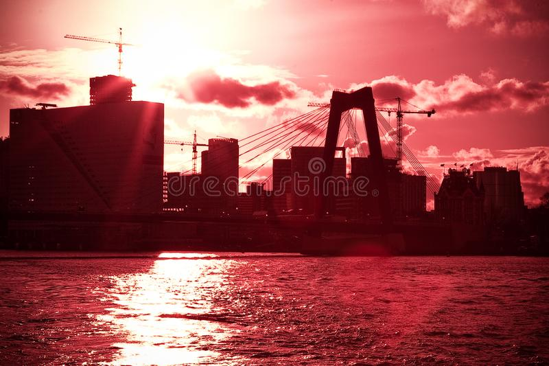 Skyline of rotterdam. Rotterdam, Netherlands - April 05, 2008 : In high contrast with a red cast we see the skyline of rotterdam from a boat on the Maas river stock photography