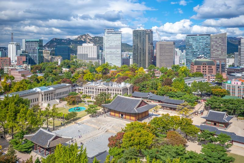 Skyline of seoul and Deoksugung palace in korea. Deoksugung Palace was the location where Prince Wolsan, older brother of King Seongjong, lived. At the time, the stock images