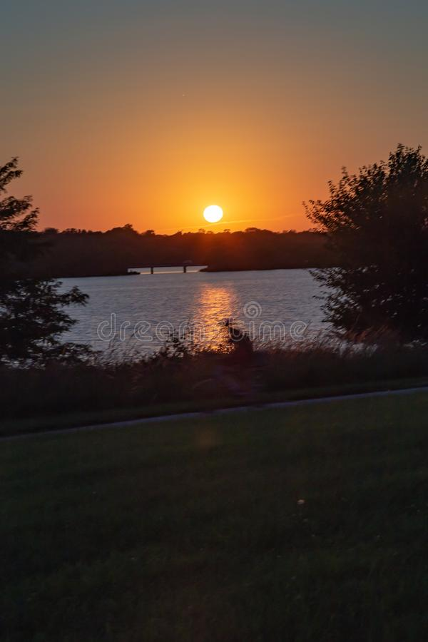 Clear outline of the sun at Sunset with beautiful skyline over lake Zorinsky Omaha Nebraska. Skyline of the setting sun with beautiful skyline and blue lake royalty free stock photos