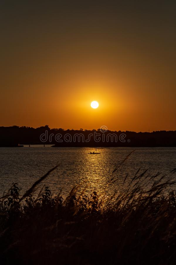 Clear outline of the setting sun at Sunset with beautiful skyline over lake Zorinsky Omaha Nebraska. Skyline of the setting sun with beautiful skyline and golden royalty free stock images