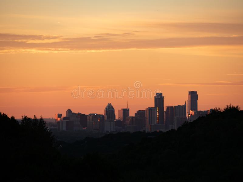 Skyline shot of Austin Texas downtown nestled between silhouetted hills stock image