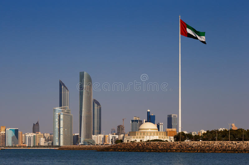 A skyline view of the Abu Dhabi including the UAE National Flag royalty free stock photos