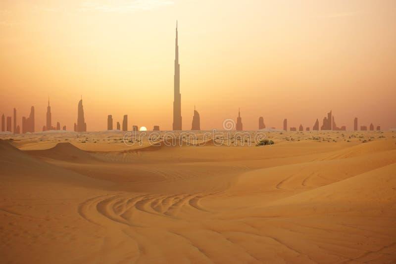 Skyline von Dubai am Sonnenuntergang oder an der Dämmerung, Ansicht von der arabischen Wüste lizenzfreie stockfotos