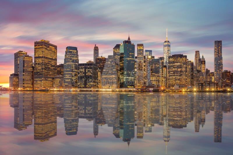 Skylines de New York City - de Manhattan no tempo da noite com reflecti foto de stock