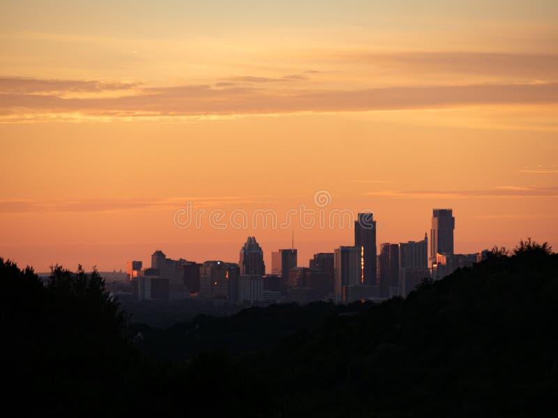 Skylineschuß von Austin Texas-Stadtzentrum angeschmiegt zwischen silhouettierten Hügeln stockbild